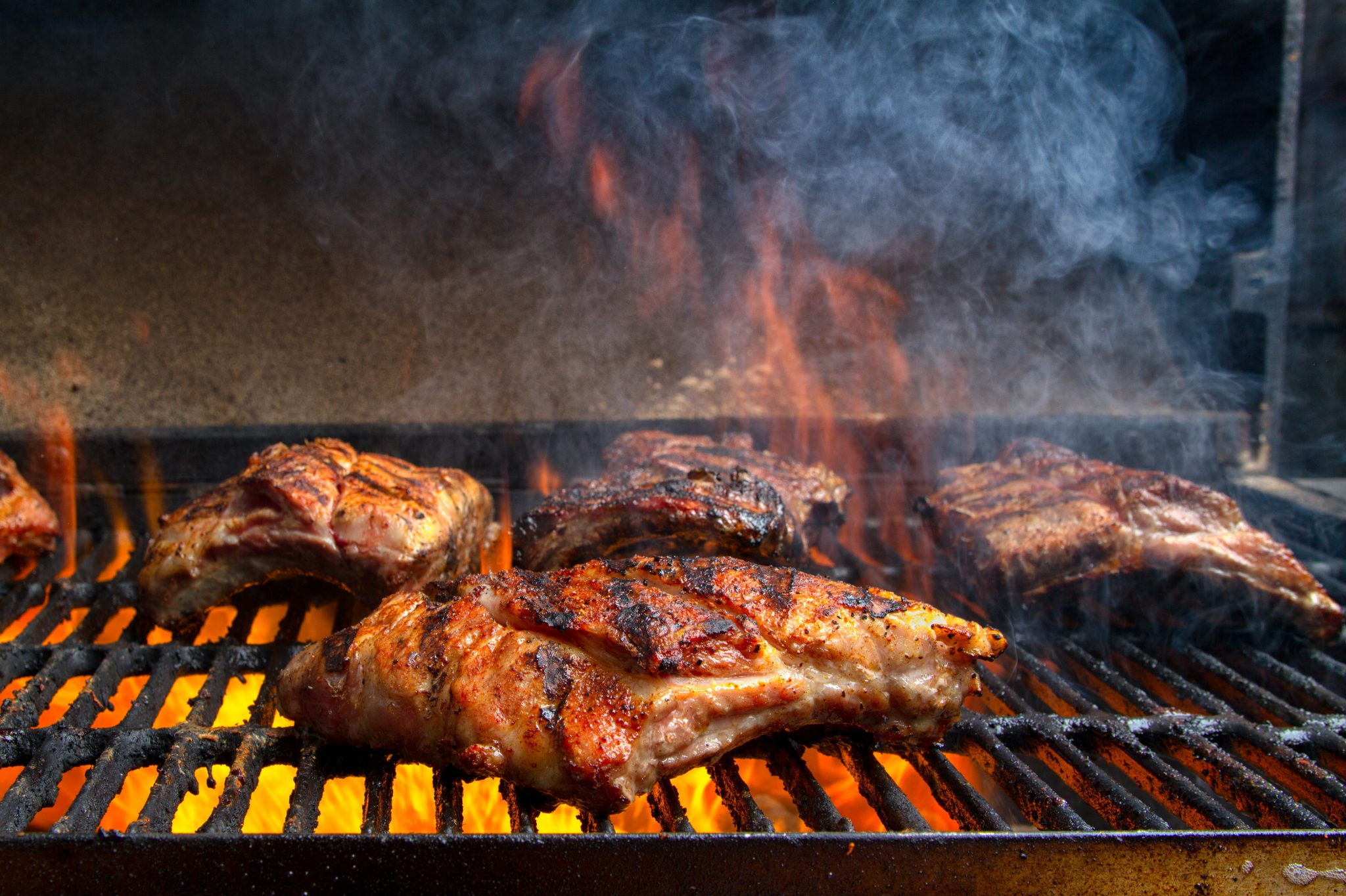 Grouping of Baby Back Ribs on a barbecue grill with flames leaping up to sear the meat sealing in the juices.  Ribs have nice grill marks and are seasoned with a dry rub and are almost ready to serve.